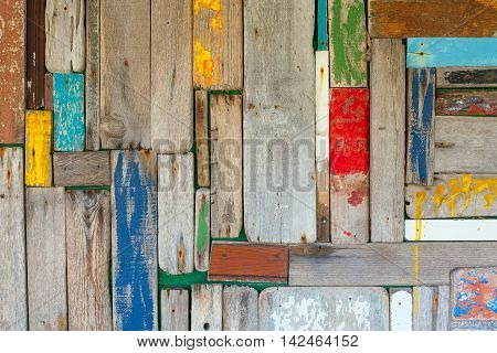 Photo of a well worn wooden wall with multicoloured planks.
