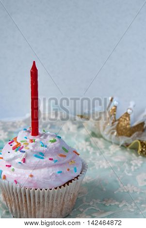 Cupcakes with red candle on the first birthday of a little girl. Against the backdrop of golden hairpin crown