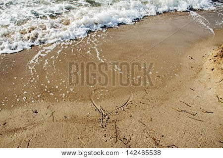 heart shape in the sunny sand beach disappears under the foam of the sea waves background concept with copy space for love and leave selected focus