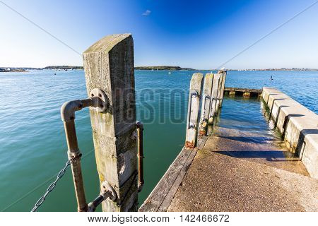 Jetty with mooring in Christchurch Harbour on a sunny day. England United Kingdom.