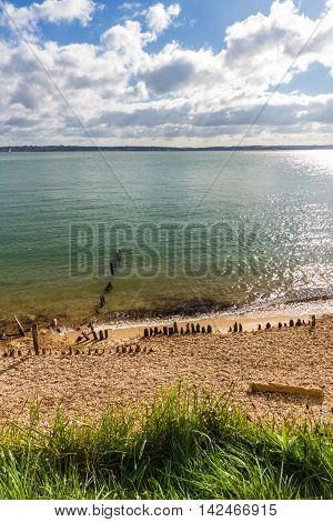 Pebble beach with worn defences and Isle of Wight in distance. Lepe Country Park Exbury Southampton Hampshire England United Kingdom