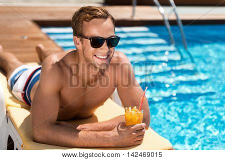 Positivity in mind. Delighted handsome joyful man drinking cocktail and lying on the sun bed while enjoying relaxation near swimming pool