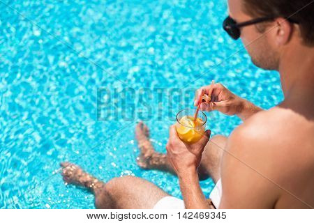 Energy booster. Close of cocktail in hands of pleasant handsome man holding it and going to drink while sitting near swimming pool