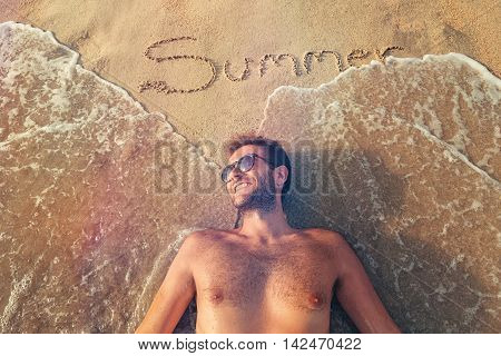 Young man lying on the beach with a word summer written on the sand