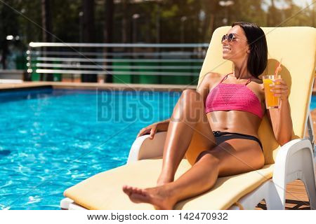 Summer paradise. Delighted relaxed smiling woman lying on the sun bed and drinking cocktail while relaxing near swimming pool