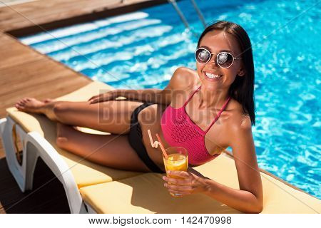 Refresh your mind. Cheerful beautiful smiling woman drinking cocktail and lying on the sun bed while resting near swimming pool