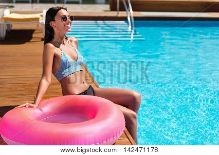 Active time spending. Joyful content smiling woman sitting near swimming pool and holding inflatable ring while resting