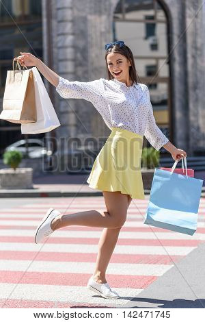 I buy everything what I want. Happy young woman is boasting with her purchase and smiling. She is standing and holding packets