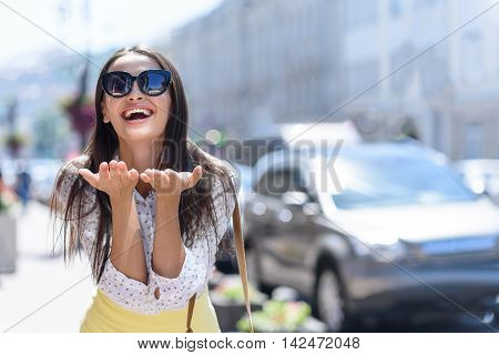 Carefree young woman is sending air kiss to camera. She is raising hands to face and smiling. Girl is standing on street in town