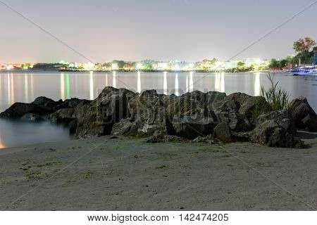 views of the glowing city lights from the shore with rocks