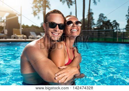 True feelings. Cheerful smiling loving couple standing in a swimming pool and embracing while resting together
