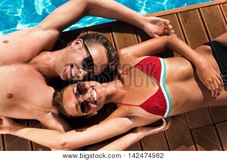 Happy together. Cheerful content smiling couple resting together and smiling while lying near swimming pool