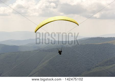 Paragliding flying in the soft blue sky.