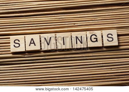 SAVINGS word written on wood block. Wooden abc