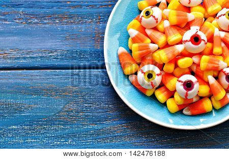 Halloween candy corns candy eyeballs on blue wooden background
