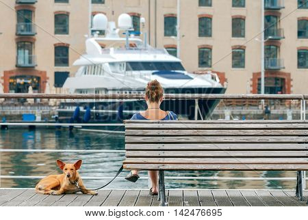 Young woman with a red dog sits on bench in the port of Genoa.