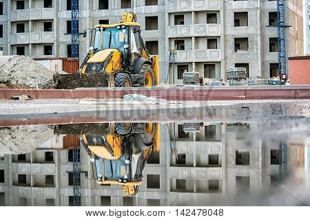 Excavator at construction site on building background