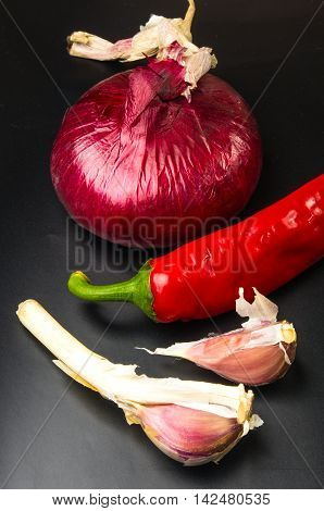 still life - sweet purple Crimean onion, garlic and Cayenne red pepper on black background