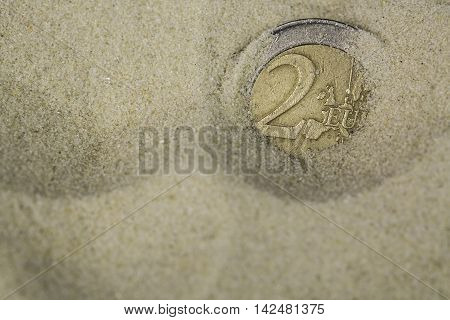 Finance concept. Euro coin swamps in the sand.