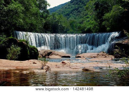 The waterfall is in a forest in the south of France and the river flows through Herault