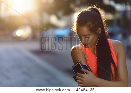 Woman Jogger Checks Her Music Device