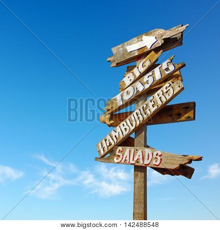 Rustic wooden signs indicating the direction to big toasts, hamburgers and salads