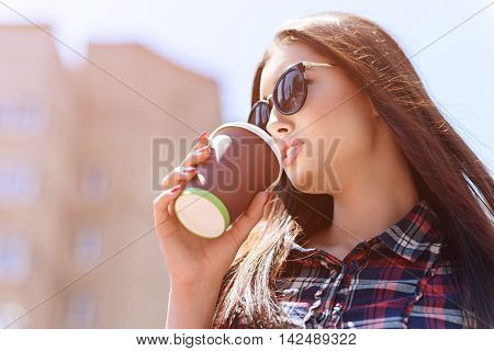 Pretty young woman is drinking hot coffee with pleasure. She is standing on street with relaxation