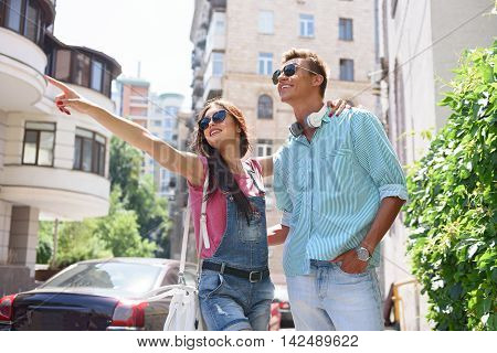 Look at that. Happy loving couple is resting in city. They are embracing and smiling. Woman is pointing finger sideways with interest