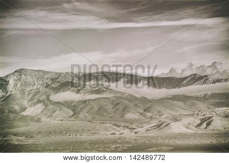 Clouds and fog pull over the peaks and ridges of a mountain or mountain range.