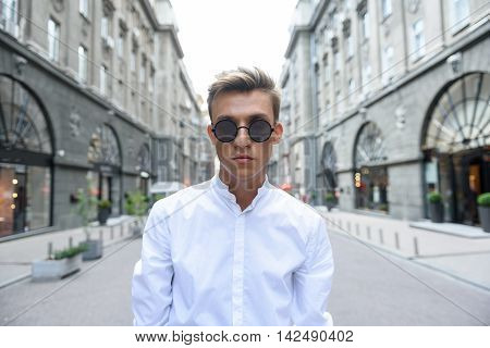 Young man is walking in city. He is looking at camera with seriousness