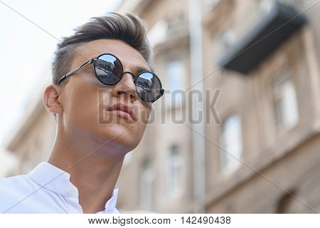 Sexy young man is looking forward with desire. He is standing in city