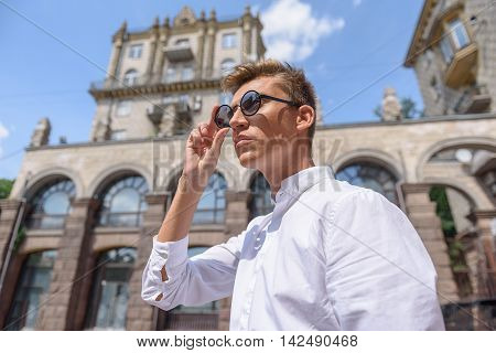 Cheerful young man is enjoying view of city. He is standing and adjusting his eyeglasses. Man is looking forward with interest