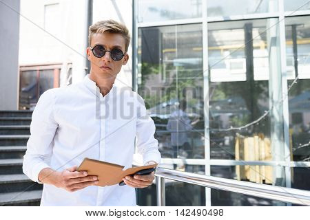Young man is using tablet and looking at camera with seriousness. He is standing near building outdoors