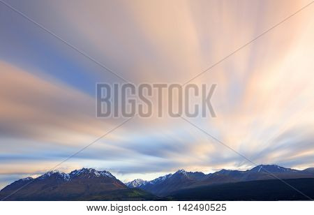 Long exposure of cloud movement above snow capped mountains.