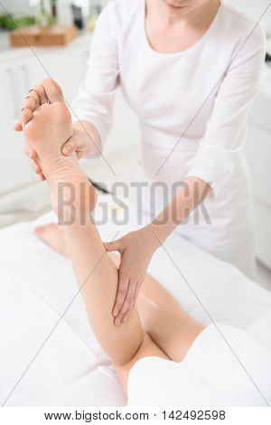 Professional masseuse pampering female leg gently. Young woman is lying on massage table at spa