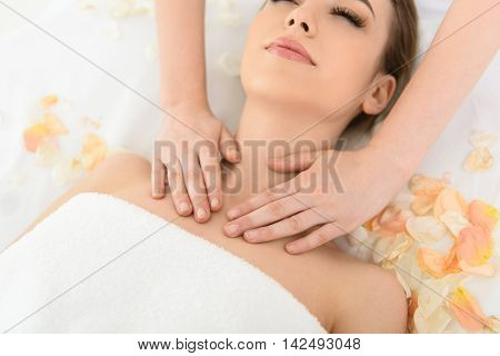 Professional beautician is massaging female neck at spa. Woman is lying near petals. Her eyes are closed with pleasure
