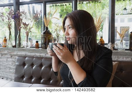 woman is sipping coffee at coffee time with wooden table and relax atmosphere