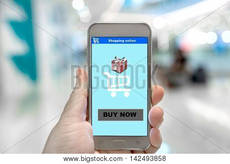 Buy now on shopping online e-business website at smartphone screen in hand e-business and technology concept