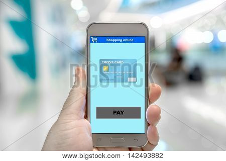 Payment now on shopping online e-business website at smartphone screen in hand e-business and technology concept