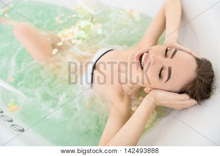 What pleasure. Happy young woman is luxuriating in jacuzzi. She is touching head and laughing. Her eyes are closed with enjoyment