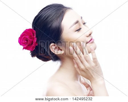 portrait of a young and beautiful asian woman with red rose in hair side view isolated on white background.
