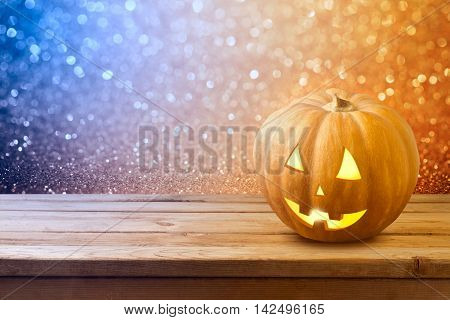 Halloween background with pumkin jack lantern on wooden table over bokeh lights