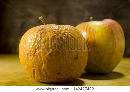Rotten and fresh apples on a wooden background