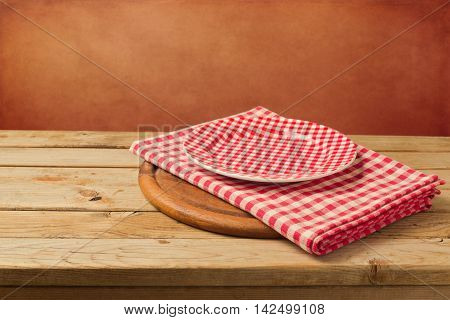 Empty checked plate and tablecloth on wooden table