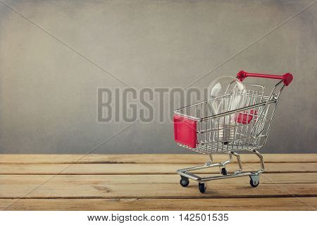 Creativity concept. Shopping cart with light bulb on wooden surface