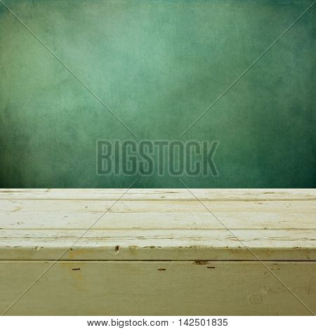 Empty white wooden table over green grunge wallpaper