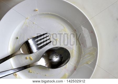 Empty white plate with a spoon and fork after a meal.