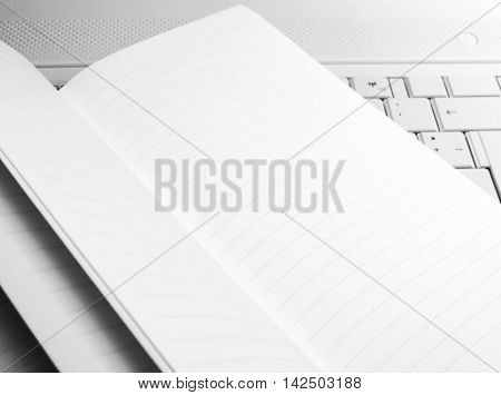 Lined note book with copy space, llying on a white laptop.