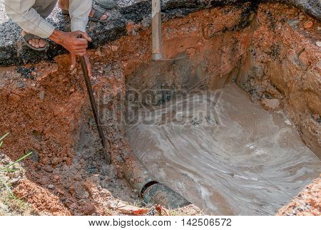 Plumbing Repair Man. Workers digging to repair water pipes at the break. hand Workers crowbar dig hole at motion water.