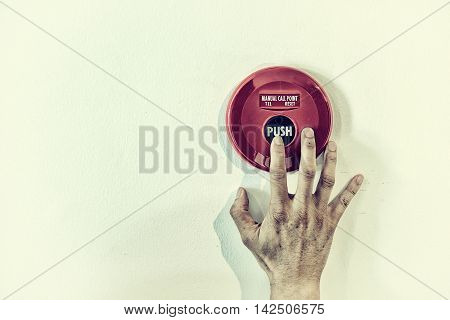 The hand of man is pushing fire alarm on the white wall in vintage color